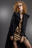 девушка с шикарными волосами и красивыми глазами в обольстительном коротком золотом платье и сером пальто в готическом стиле Стоковое фото RF
