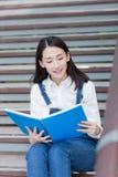 девушка outdoors читая Стоковая Фотография