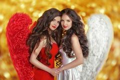 2 девушки ангелов моды красивых моделируют с курчавыми длинными волосами Стоковая Фотография RF