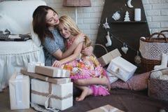 2 девушки дают подарки одина другого, объятия, подготовку для рождества, украшение, оформление, образ жизни, семью, семейные ценн Стоковая Фотография