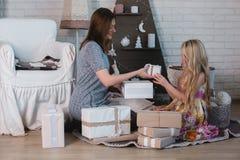 2 девушки дают подарки одина другого, объятия, подготовку для рождества, украшение, оформление, образ жизни, семью, семейные ценн Стоковые Фото
