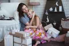 2 девушки дают подарки одина другого, объятия, подготовку для рождества, украшение, оформление, образ жизни, семью, семейные ценн Стоковые Фотографии RF