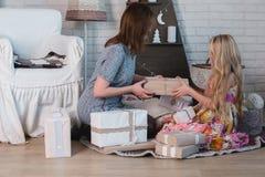 2 девушки дают подарки одина другого, объятия, подготовку для рождества, украшение, оформление, образ жизни, семью, семейные ценн Стоковое Изображение RF
