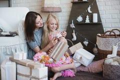 2 девушки дают подарки одина другого, объятия, подготовку для рождества, украшение, оформление, образ жизни, семью, семейные ценн Стоковое Изображение