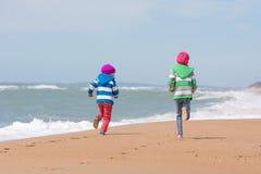 2 девушки бегут гонка на взморье пляжа Стоковые Фото