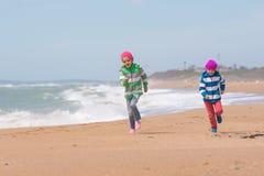 2 девушки бежать на взморье пляжа Стоковое Изображение