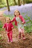 2 девушки бежать через древесины Bluebell совместно Стоковая Фотография