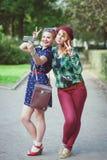 2 девушки битника при расчалки фотографируя на m Стоковая Фотография