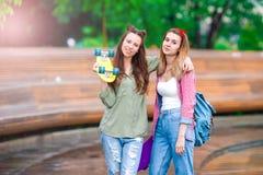2 девушки битника с скейтбордом outdoors в свете захода солнца Активные sporty женщины имея потеху совместно в парке конька Стоковое Изображение RF