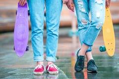 2 девушки битника с скейтбордом outdoors в свете захода солнца Skatebords крупного плана в женских руках Активные sporty женщины Стоковая Фотография