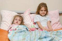 2 девушки больной в кровати с термометром Стоковая Фотография RF