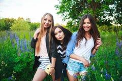 3 девушки блондинка и брюнет битников принимая автопортрет на фотокамере Поляроид и усмехаться внешний Девушки имея потеху совмес Стоковые Фото