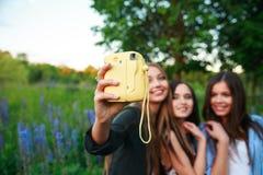 3 девушки блондинка и брюнет битников принимая автопортрет на фотокамере Поляроид и усмехаться внешний Девушки имея потеху совмес Стоковое Фото