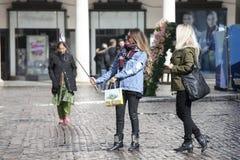2 девушки: блондинка и брюнет, делают selfie телефоном в середине улицы перед внешними витринами магазина Стоковая Фотография RF