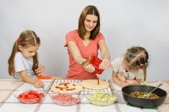2 девушки восторженно наблюдаемой как мама льют основу кетчуп для пиццы Стоковое Изображение