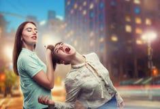 2 девушки волочат один другого для волос на улице города Стоковое Фото