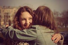 2 девушки встречанной на улице и смехе Стоковые Изображения