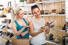 2 девушки выбирая ботинки в магазине Стоковая Фотография