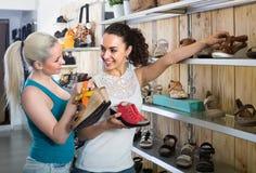 2 девушки выбирая ботинки в магазине Стоковые Фотографии RF