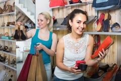 2 девушки выбирая ботинки в магазине Стоковые Фото