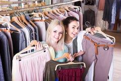 2 девушки выбирая одежды Стоковые Фото