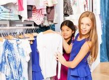 2 девушки выбирая правый деталь во время покупок Стоковая Фотография RF