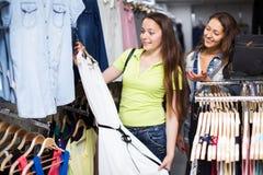 2 девушки выбирая платье в магазине Стоковая Фотография RF