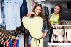 2 девушки выбирая платье в магазине Стоковое фото RF