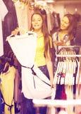 2 девушки выбирая платье в магазине Стоковые Фото