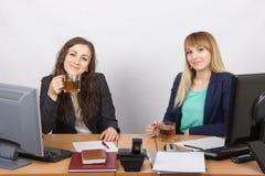 2 девушки выпивают чай, офис за столом Стоковые Фотографии RF