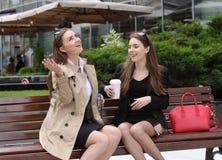 2 девушки выпивая coffe на скамейке в парке Стоковые Изображения