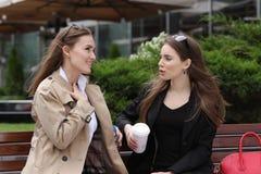 2 девушки выпивая coffe на скамейке в парке Стоковые Фотографии RF