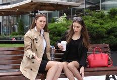 2 девушки выпивая coffe на скамейке в парке Стоковое Изображение RF
