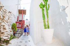 2 девушки в голубых платьях имея потеху outdoors в греческой традиционной деревне Стоковые Фото