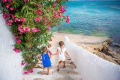 2 девушки в голубых платьях имея потеху outdoors Дети на улице типичной греческой традиционной деревни с белыми стенами и Стоковое фото RF