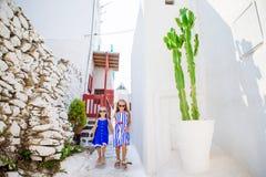 2 девушки в голубых платьях имея потеху outdoors Дети на улице типичной греческой традиционной деревни с белыми стенами и Стоковые Изображения RF