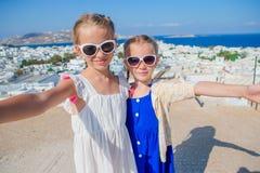 2 девушки в голубых платьях принимая фото selfie outdoors Ягнит предпосылка типичной греческой традиционной деревни с белизной Стоковое Изображение RF