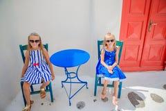 2 девушки в голубых платьях сидя в внешнем кафе на улице типичной греческой деревни на острове Mykonos, Греции Стоковые Фото