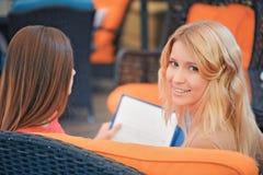 2 девушки в кафе смотря через меню Стоковые Фотографии RF