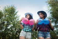 2 девушки в ковбойских шляпах с воздушными шарами Стоковая Фотография