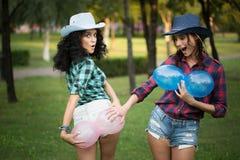 2 девушки в ковбойских шляпах с воздушными шарами Стоковое Изображение