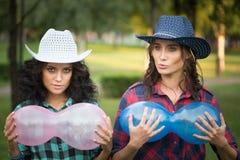 2 девушки в ковбойских шляпах с воздушными шарами Стоковые Изображения RF