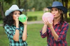 2 девушки в ковбойских шляпах с воздушными шарами Стоковое Фото
