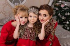 3 девушки в красном платье вечера рождественская елка Стоковые Фотографии RF
