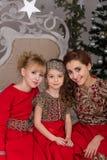 3 девушки в красном платье вечера рождественская елка Стоковое фото RF