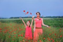 2 девушки в красном платье идя на мак field весной Стоковые Фото