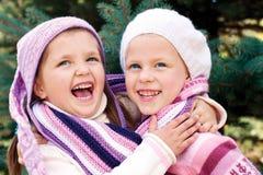 2 девушки в красочной связанной одежде обнимая около Christma Стоковые Изображения