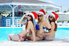 3 девушки в купальных костюмах и крышках Санта Клауса на предпосылке бассейна Стоковые Изображения