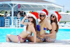 3 девушки в купальных костюмах и крышках Санта Клауса на предпосылке бассейна Стоковое фото RF