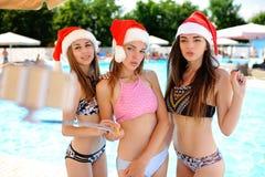 3 девушки в купальных костюмах и крышках Санта Клауса на selfie снимают предпосылку бассейна Стоковые Изображения